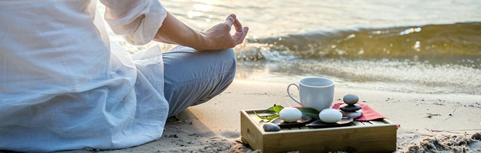 Meditations-Urlaub, Frau meditiert am Strand