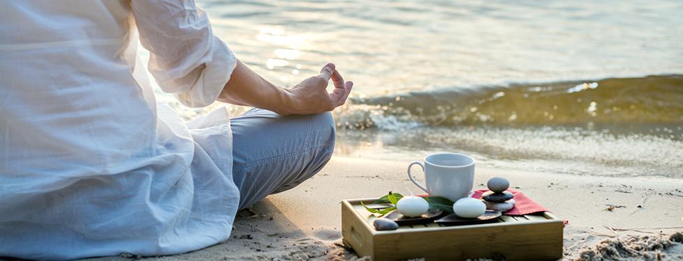 Meditationsurlaub - Frau am Strand beim Meditieren